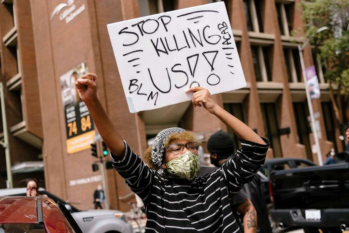 A protestor holds a sign during a Justice for George Floyd & Breonna Taylor Car Caravan in Oakland, Calif, on Sunday, May 31, 2020.