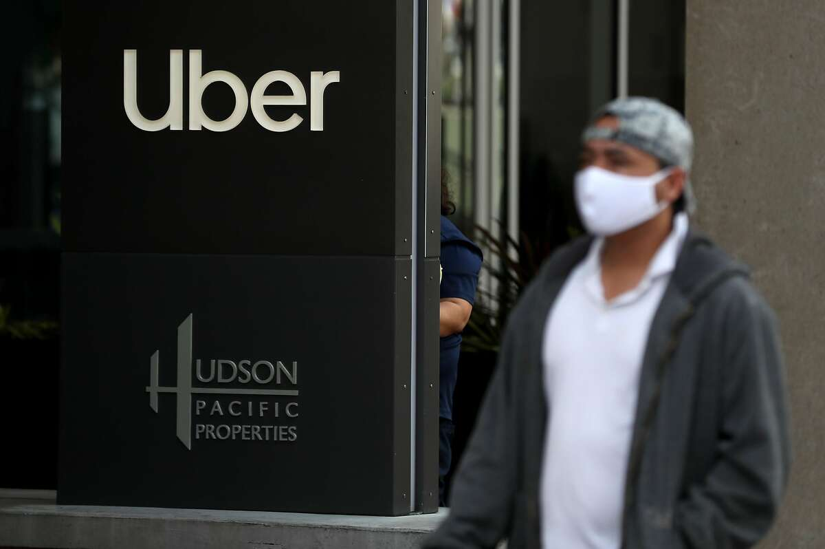 SAN FRANCISCO, CALIFORNIA - MAY 18: A pedestrian walks by a sign in front of the Uber headquarters on May 18, 2020 in San Francisco, California. Uber announced plans to cut 3,000 jobs and shutter or consolidate 40 offices around the world due to severely declining business as the coronavirus (COVID-19) pandemic continues. The cuts come two weeks after Uber cut 3,700 employees. (Photo by Justin Sullivan/Getty Images)