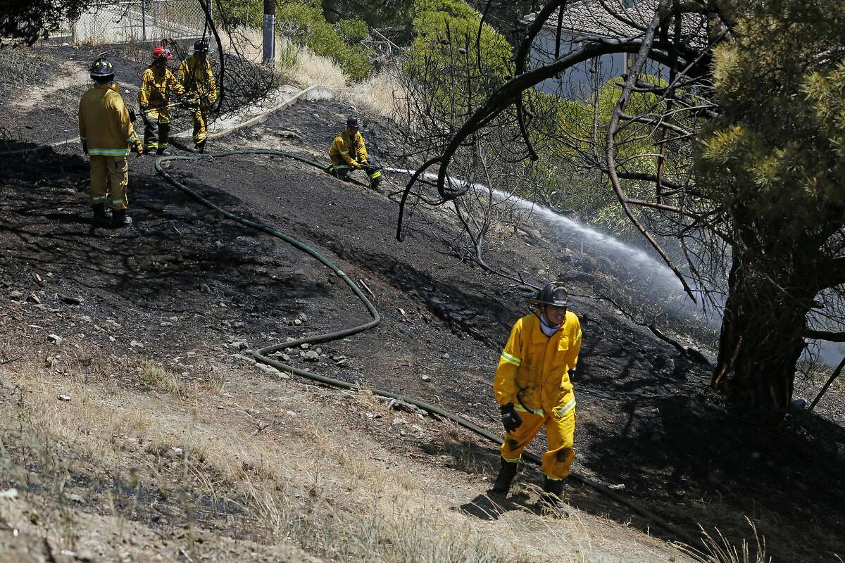 Firefighters continue to pour water on a grass fire off 23rd and Dakota streets on Friday, June 5, 2020, in San Francisco, Calif. A grass fire prompted an evacuation of homes along Dakota Street. The fire is contained.