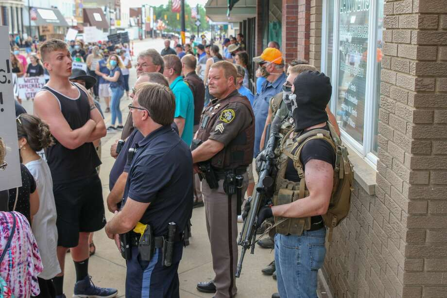 Tensions mount as local residents stand by with firearms during a social injustice rally Friday, June 5. Photo: Eric Young/Huron Daily Tribune / © Huron Daily Tribune 2020