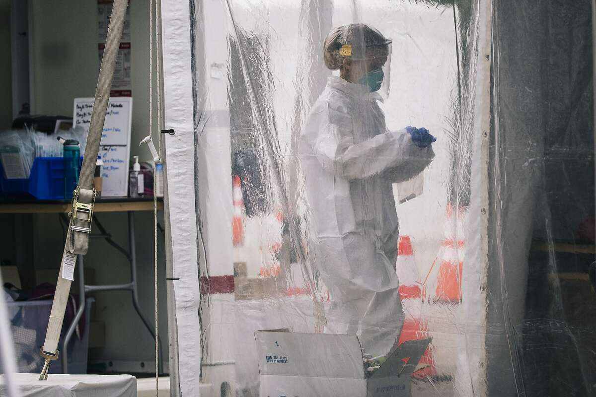 A medical worker carries a sample to test for COVID-19 novel coronavirus at CityTestSF Soma in San Francisco, Calif. on Friday, June 5, 2020.