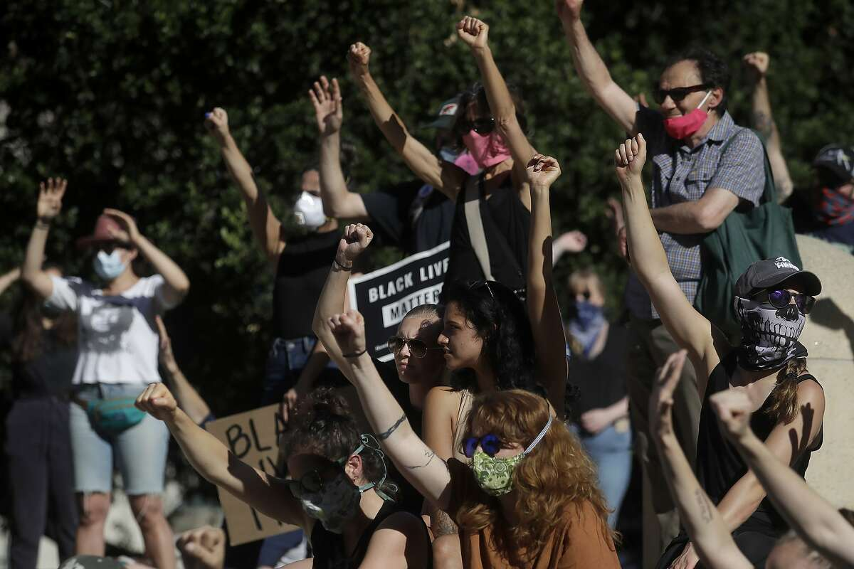 People raise their hands as they listen to a speaker in Oakland, Calif., Thursday, June 4, 2020, during a protest over the death of George Floyd, who died May 25 after being restrained by police in Minneapolis. (AP Photo/Jeff Chiu)