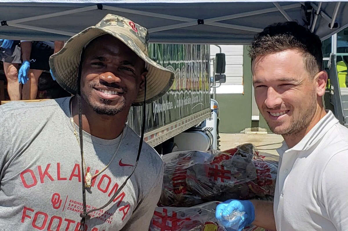 Astros third baseman Alex Bregman (right) and NFL veteran Adrian Peterson distribute food packages Friday to families in Spring Branch.
