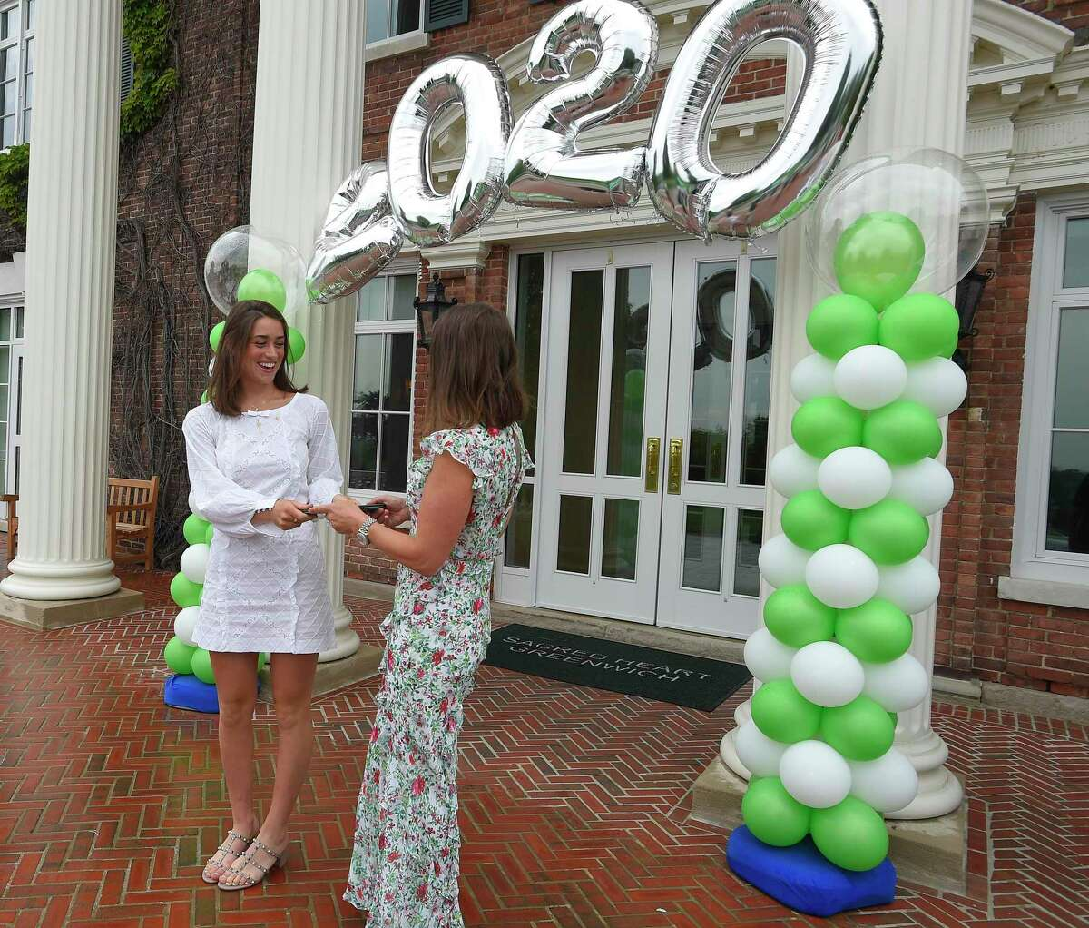 Emma Caruso and her mother Sandra Caruso, a trustee at Sacred Heart Greenwich, pose for a photograph as the Class of 2020 celebrates with a Graduation Parade at the school in Greenwich, Connecticut on June 5, 2020. Each Senior was presented with their diplomas and had a photograph taken with a celebratory display in front of the school's Salisbury Hall. After distance learning to close the year due to the coronavirus, Greenwich's private schools have set Sept. 8 to reopen with flexible plans to try and get students back on campus if it is safe.