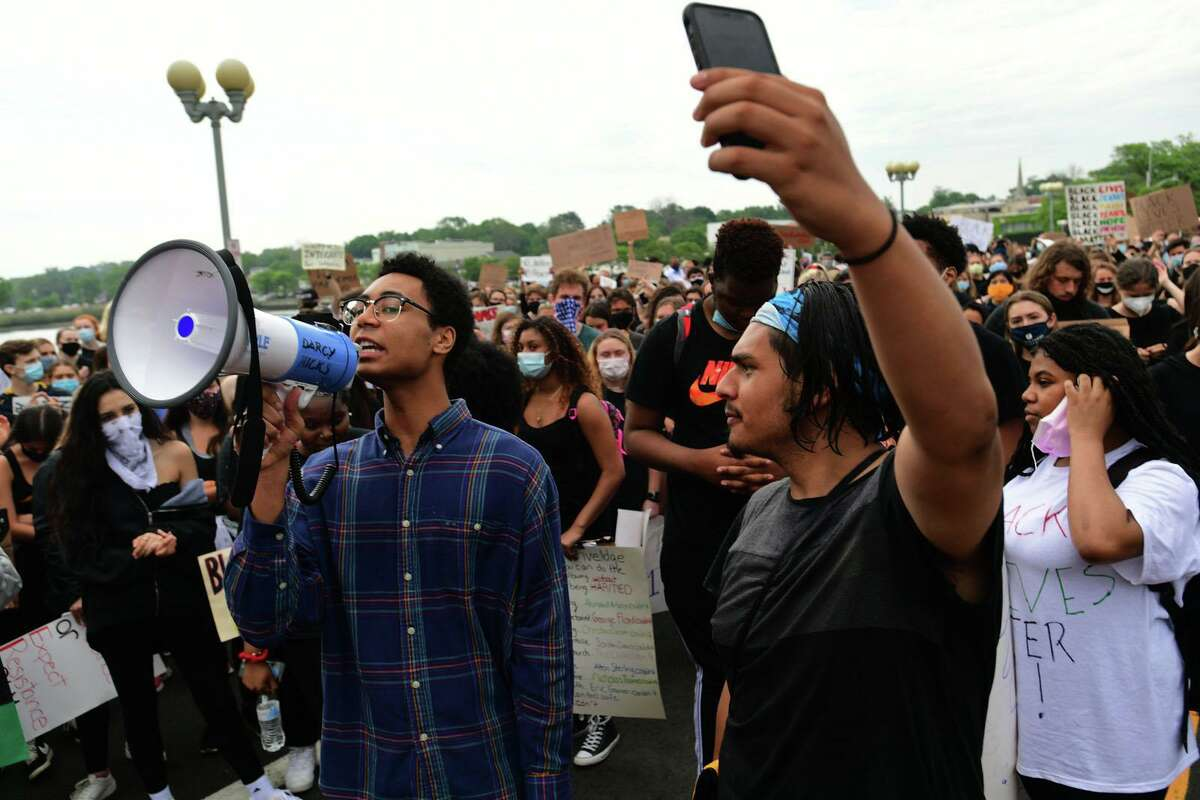 Black Lives Matter and several current and formet Staples High School students including Chet Ellis join a group of protestors Friday, June 5, 2020, in downtown Westport, Conn. The group marched from the Post Road bridge to the police station in a peaceful protest against police brutality.