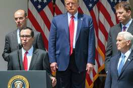 President Donald Trump, Vice President Mike Pence and other aides listen as Treasury Secretary Steven Mnuchin speaks in the Rose Garden of the White House on Friday.