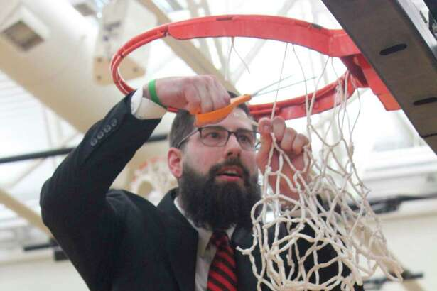 Ferris men's basketball coach Andy Bronkema cuts down the net at Wink Arena after his team clinched the GLIACtitle in March. With theongoing Coronavirus episode, Bronkema continues to work from home while awaiting the chance to see his team again. (Pioneer file photo)