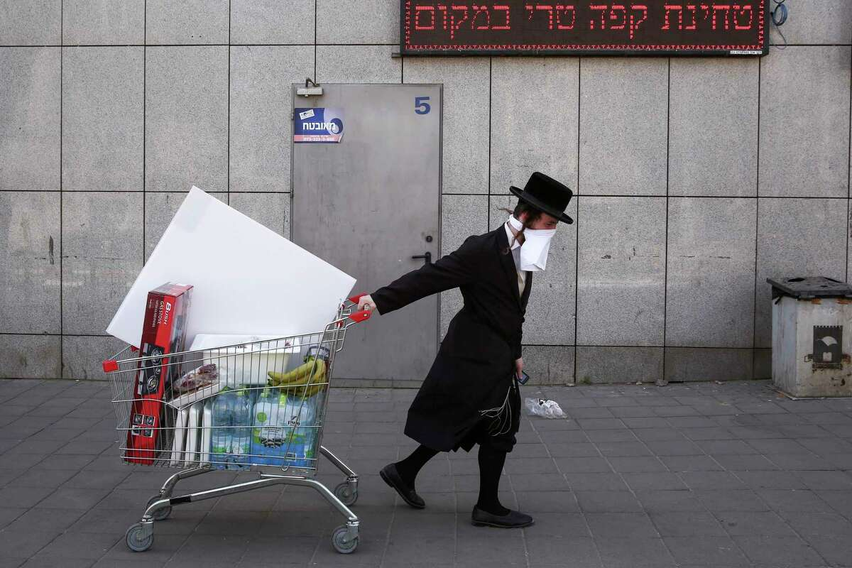 FILE - In this April 3, 2020, file photo, an ultra-Orthodox Jew wears an improvised protective face mask as he pulls a supermarket cart on a mainly deserted street because of the government's measures to help stop the spread of the coronavirus, in Bnei Brak, a suburb of Tel Aviv, Israel. That's the harsh truth facing workers laid off around the world, from software companies in Israel to restaurants in Thailand and car factories in France, whose livelihoods fell victim to a virus-driven recession that's accelerating decline in struggling industries and upheaval across the global workforce. (AP Photo/Oded Balilty, File)