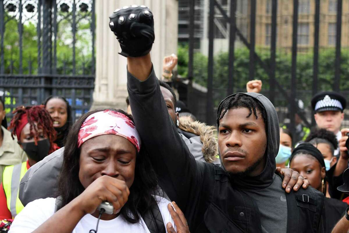 TOPSHOT - Protestors including British actor John Boyega (C) raise their fists in Parliament square during an anti-racism demonstration in London, on June 3, 2020, after George Floyd, an unarmed black man died after a police officer knelt on his neck during an arrest in Minneapolis, USA. - Londoners defied coronavirus restrictions and rallied on Wednesday in solidarity with protests raging across the United States over the death of George Floyd, an unarmed black man who died during an arrest on May 25. (Photo by DANIEL LEAL-OLIVAS / AFP) (Photo by DANIEL LEAL-OLIVAS/AFP via Getty Images)
