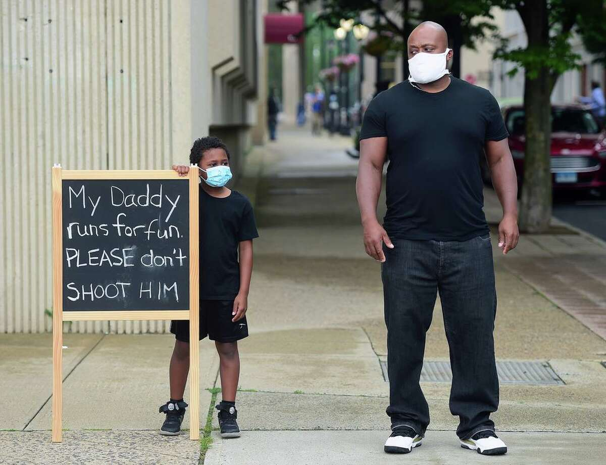 A man and a child watch a march protesting police brutality and the killing of George Floyd organized by the Citywide Youth Coalition and Black Lives Matter New Haven head down State Street toward the New Haven Police Department on June 5, 2020.