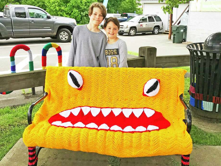 """Knitting and crocheting enthusiasts from East Hampton, Hebron and Marlborough joined students from Epoch Arts in creating a special fiber arts installation for the public. Michael and Brooke Bellemare stand behind the """"butt monster"""" bench. Photo: Contributed Photo"""