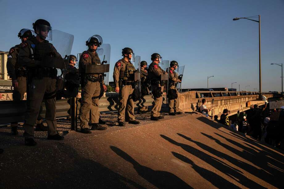 State troopers stand guard next to Interstate 35 in Austin to prevent demonstrators from blocking traffic during a Thursday protest. Photo: Photo By Tamir Kalifa For The Washington Post / For The Washington Post