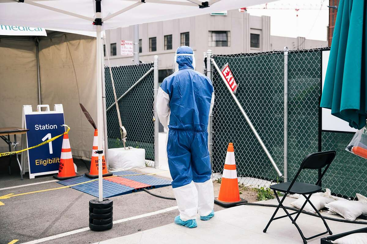 A medical worker in full personal protective equipment (PPE) stands by the entrance to a COVID-19 novel coronavirus testing site at CityTestSF Soma in San Francisco, Calif. on Friday, June 5, 2020.