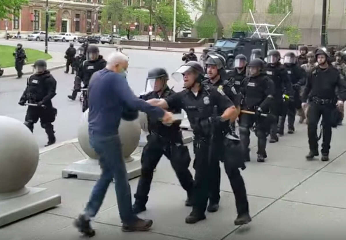 In this image from video provided by WBFO, a Buffalo police officer appears to shove a man who walked up to police Thursday, June 4, 2020, in Buffalo, N.Y. Video from WBFO shows the man appearing to hit his head on the pavement, with blood leaking out as officers walk past to clear Niagara Square. Buffalo police initially said in a statement that a person a€œwas injured when he tripped & fell,a€ WIVB-TV reported, but Capt. Jeff Rinaldo later told the TV station that an internal affairs investigation was opened. Police Commissioner Byron Lockwood suspended two officers late Thursday, the mayora€™s statement said. (Mike Desmond/WBFO via AP)