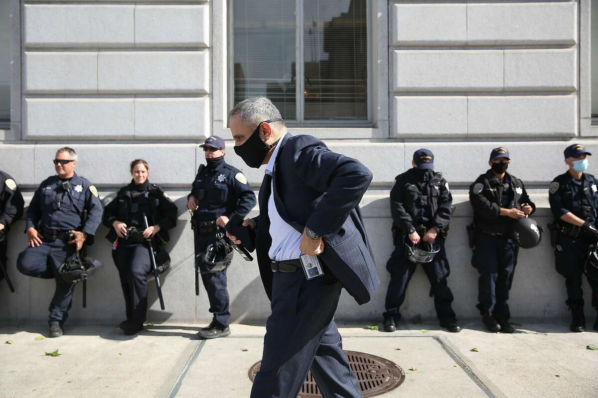 Tom‡s Aragon, director Population Health Division; Health Officer; City and County of San Francisco; walks past a line of police officers working on the peripheral of a protest as he walks on Grove Street as he returns to his office after having his portrait taken on Friday, June 5, 2020 in San Francisco, Calif.