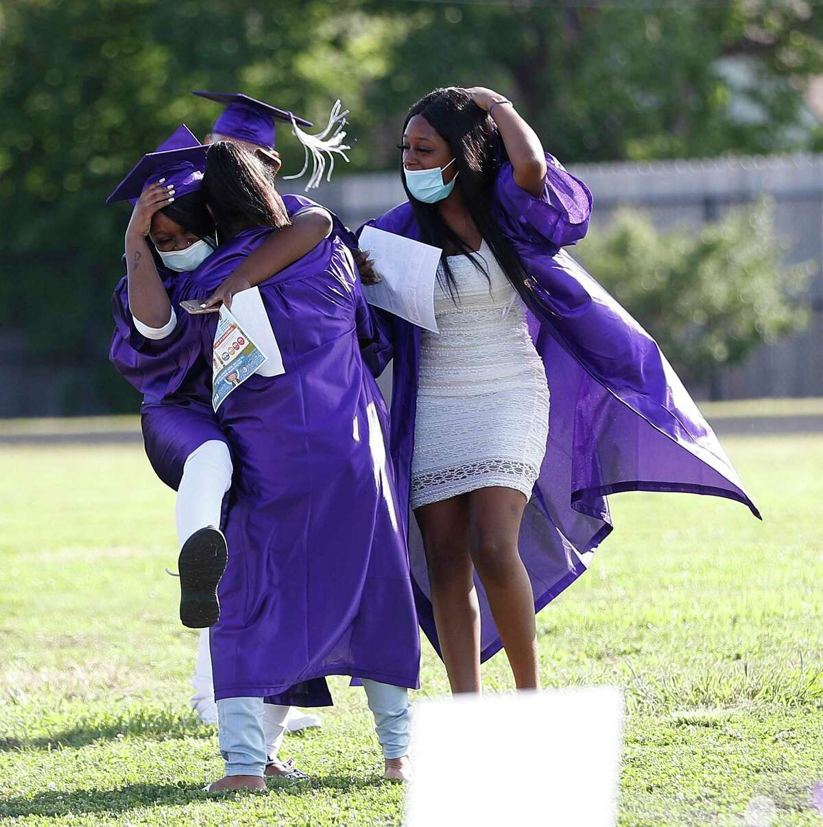 Graduating seniors hug as they get seated during the virtual graduation ceremony at Wheatley High School.