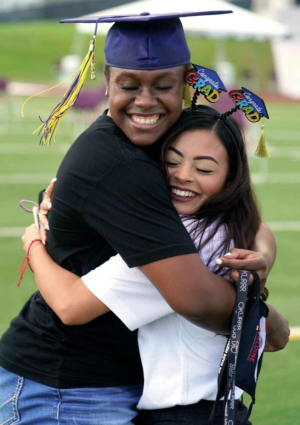 Nimitz High School seniors Tyra Davis and Aracely Hernandez hug at the graduation celebration at W.W. Thorne Stadium.
