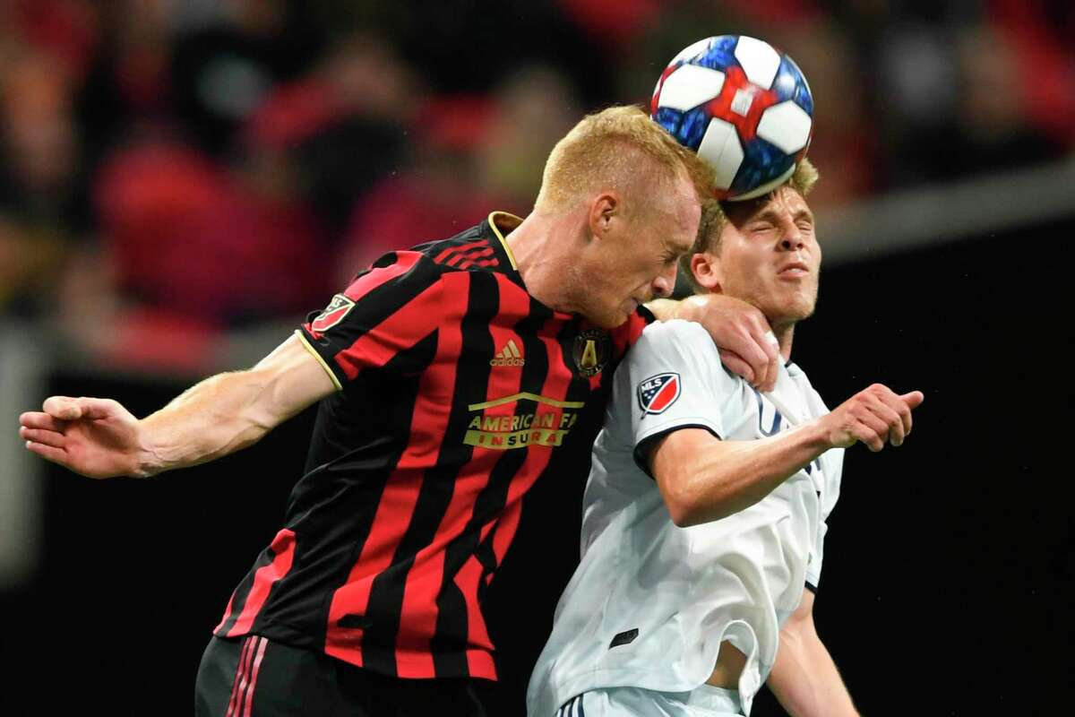 FILE - In this Oct. 19, 2019, file photo, Atlanta United defender Jeff Larentowicz, left, and New England Revolution midfielder Scott Caldwell battle for a header during round one of an MLS Cup playoff soccer game in Atlanta. Atlanta United veteran defender Jeff Larentowicz, who serves as an executive board member for the players union, said Thursday, June 4, 2020, he has safety concerns about an agreement announced Wednesday for a MLS tournament in Orlando in July. He is worried about the ongoing coronavirus pandemic and said