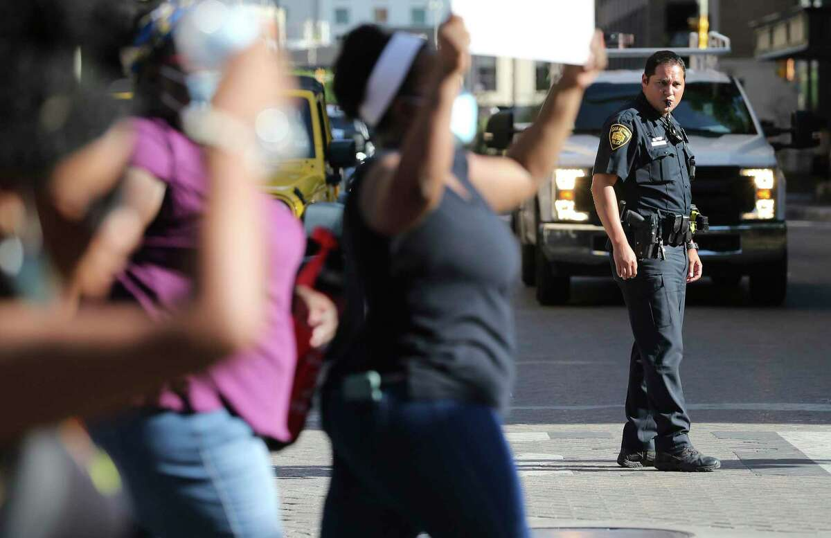 A San Antonio Police officer controls traffic as protestors march from the Bexar County Courthouse back to City of San Antonio Public Safety Headquarters on Friday, June 5, 2020. The death of African-American George Floyd at the hands of Minneapolis police last week has sparked national outrage and protests around racial inequality and police violence against people of color. San Antonio has had its share of protests demanding changes to policing policies and systemic racism.