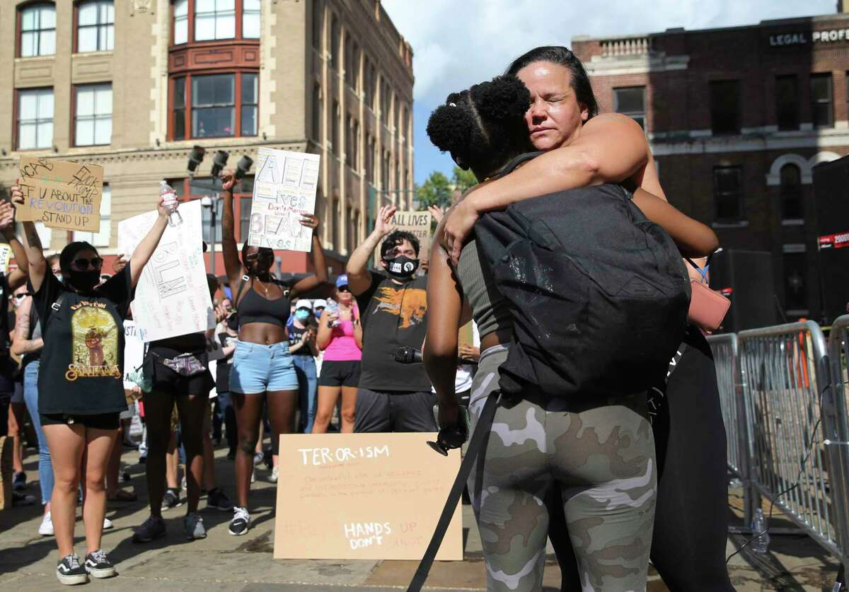 Jolene Garcia (right) receives a hug after making an impassioned speech as protestors gather at the Bexar County Courthouse on Friday. The death of an African-American man at the hands of Minneapolis police last week has sparked national outrage and protests against racial inequality and police violence.