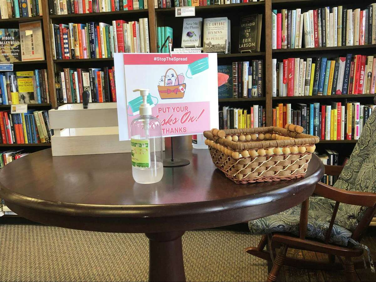 There is hand sanitizer and a box with masks on the table right inside Blue Willow Bookshop as an added measure of safety.