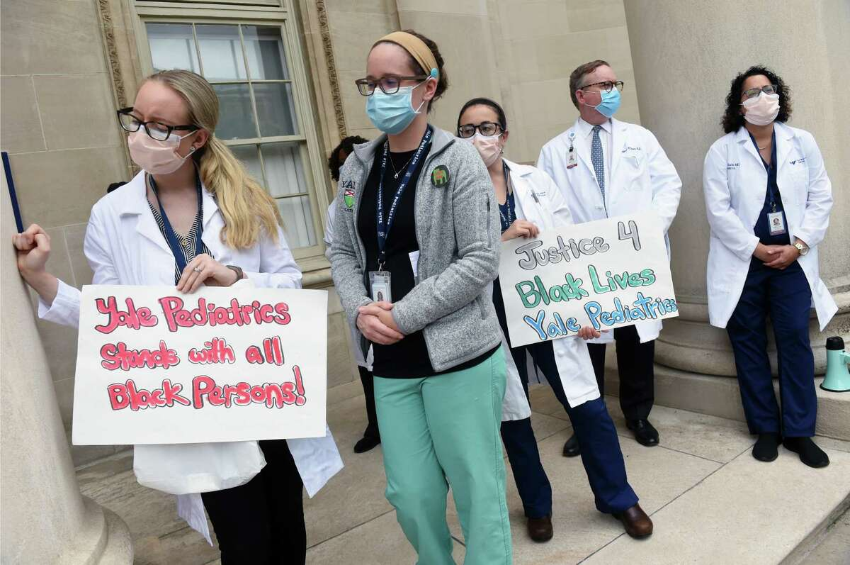Yale New Haven Hospital medical workers listen to protest organizer Dr. Amanda Calhoun speaks at the White Coats for Black Lives demonstration in front of the Yale School of Medicine in New Haven on June 5, 2020.
