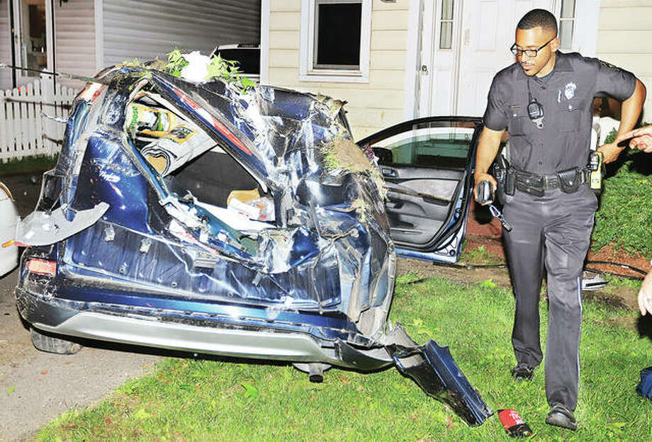 An Alton Police officer checks out the Honda SUV, model unidentifiable, that stuck the guardrail on the curve from Milton Road to westbound Brown Street about 10:15 Friday night. The vehicle flipped multiple times, struck a parked car in a driveway and stopped just short of hitting a house, seriously injuring the driver and lone occupant in the vehicle.