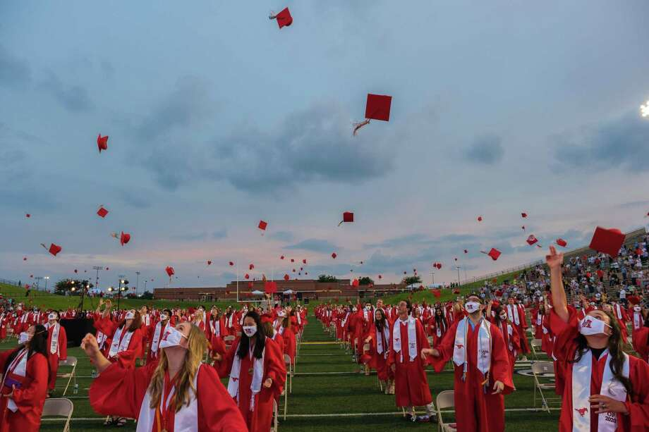 The new Memorial High School graduates throw their caps in the air at the conclusion of the class of 2020 graduation ceremony at Darrell Tully Stadium on June 1 Photo: Spring Branch Independent School District / FRED AGHO