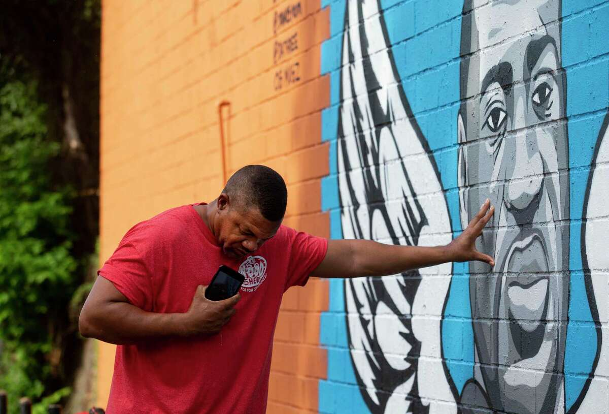 Paul Steward bows his head and touches the mural of former Houston resident George Floyd while in a moment of prayer in Third Ward.