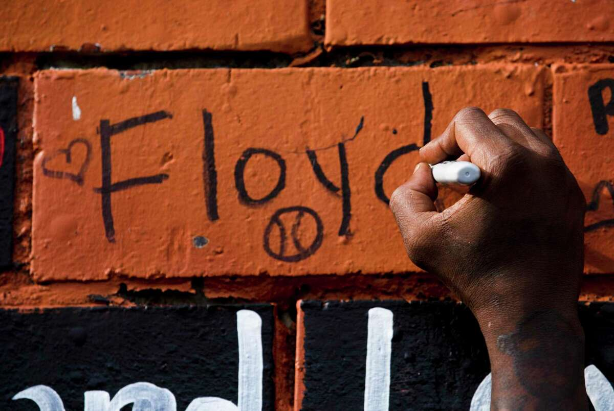 """Cal Wayne writes Floyd on """"The Wall,"""" which serves as a memorial for Cuney Homes residents in Houston's Third Ward who have died. Wayne grew up with Floyd, who died in custody of Minneapolis Police officers May 25."""