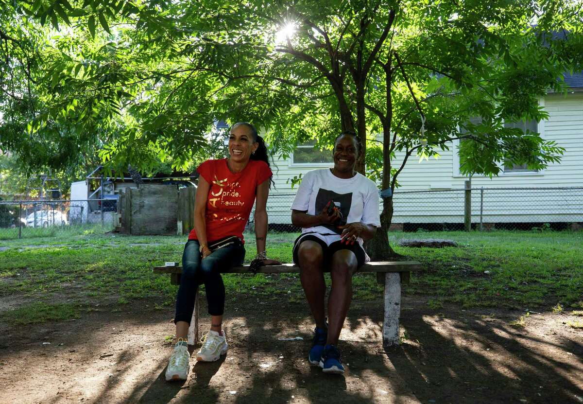 Deshae Simmons, left, and Kim Hewitt sit on a bench as they listen to 2Pac's