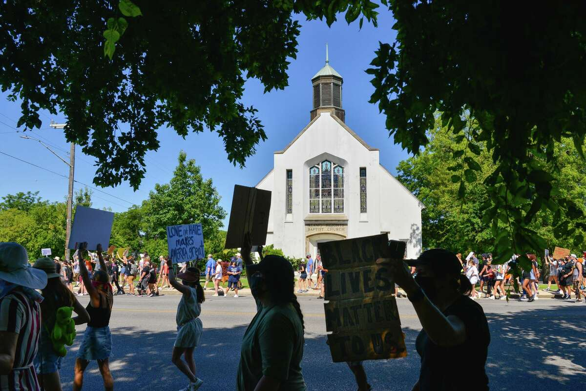 Protesters carry signs in front of the Alamo Heights Baptist Church during a Black Lives Matters march along Broadway St. Saturday morning.