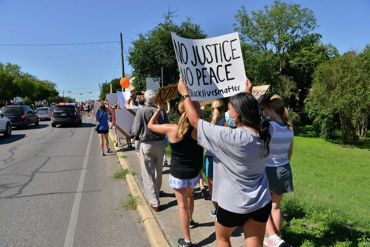 Protesters carry signs during a Black Lives Matters march along Broadway St. through Alamo Heights Saturday morning.
