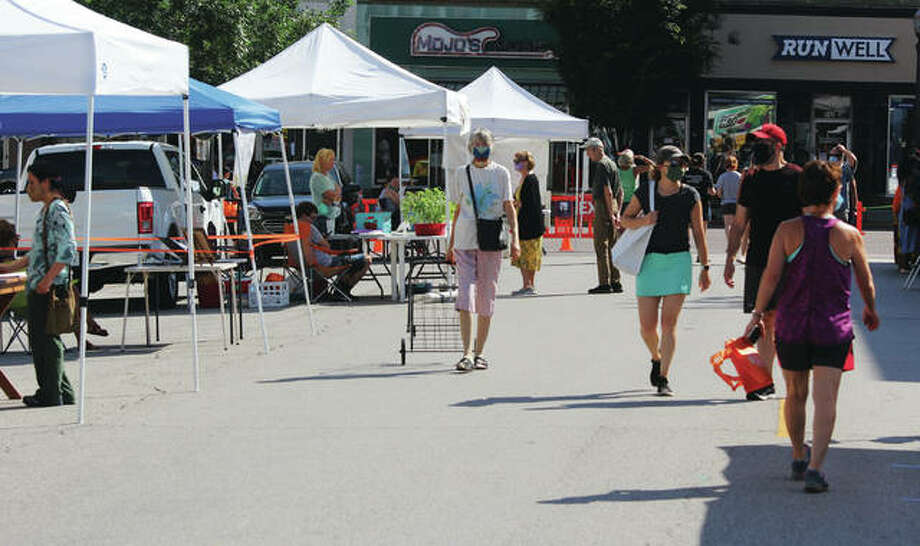 Customers make their way among stalls at the Land of Goshen Community Market in Edwardsville Saturday. The market, a Saturday staple of downtown Edwardsville for years, had been unable to open because of the coronavirus pandemic. Organizers worked out an arrangement with the city to limit access and space out customers and vendors, and the market reopened Saturday.