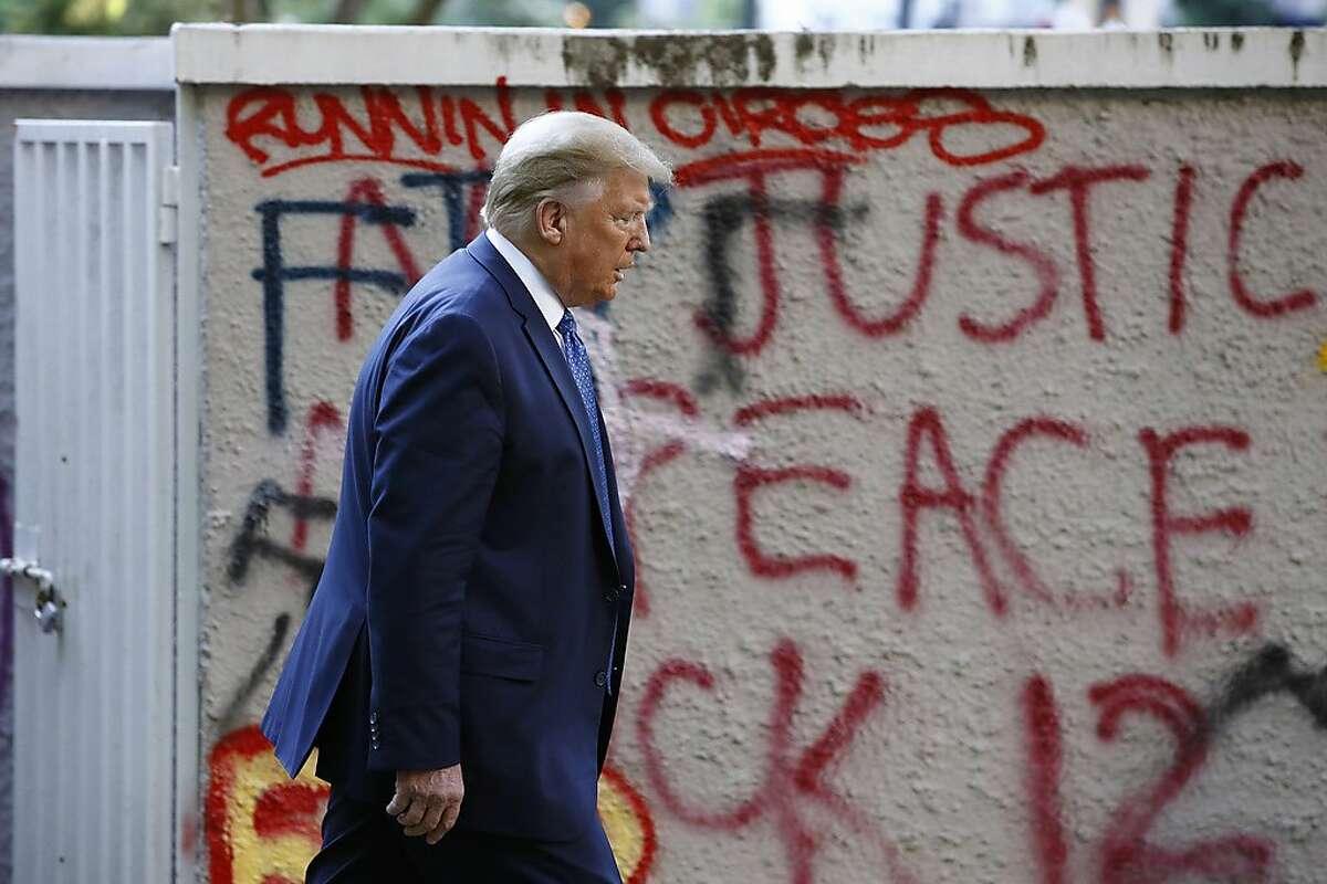 President Donald Trump walks from the White House past graffiti in Lafayette Park to visit St. John's Church in Washington on Monday, June 1, 2020. (AP Photo/Patrick Semansky)