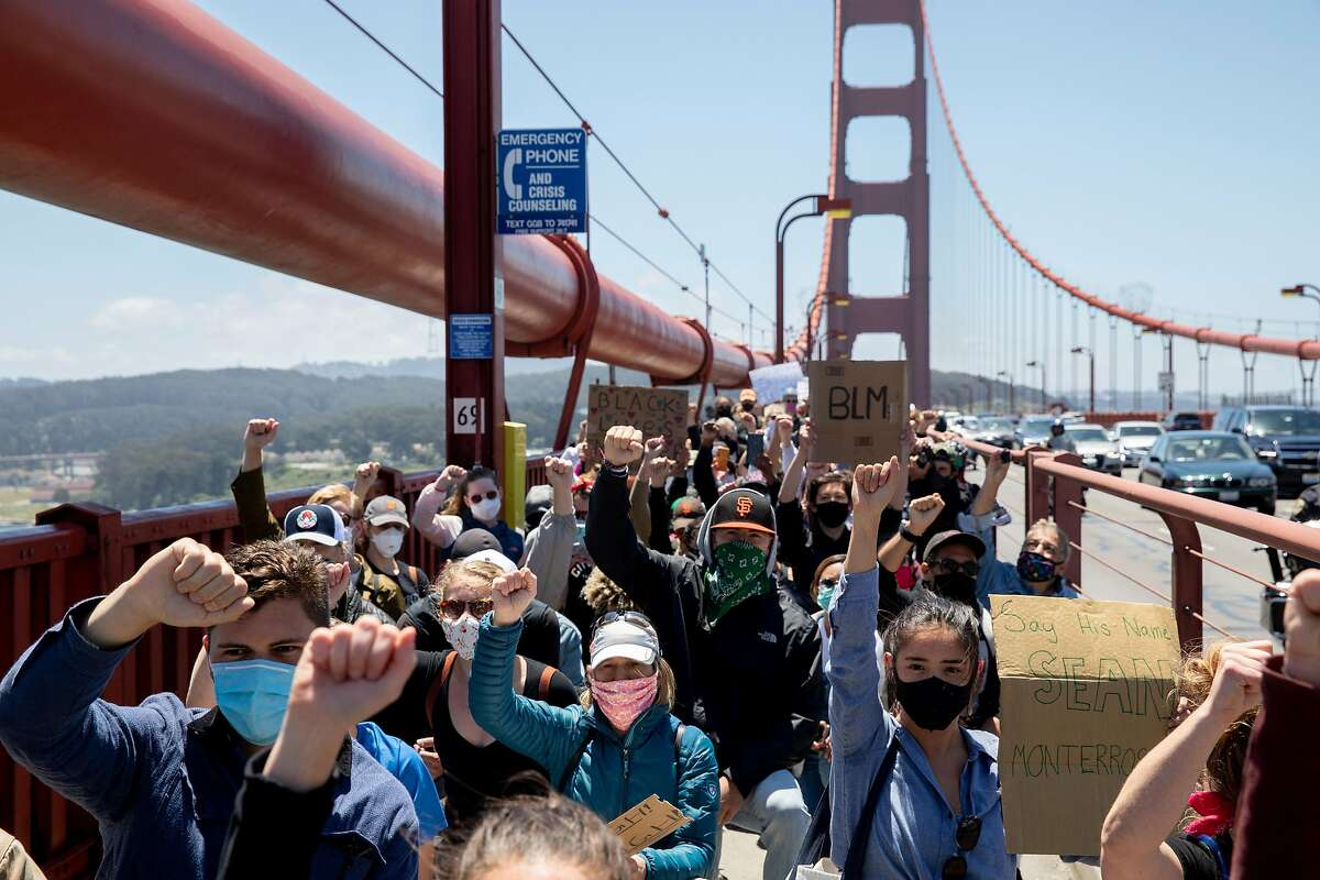 Thousands of demonstrators raise their fists and pause to take a knee as they make their way across the Golden Gate Bridge in San Francisco, Calif. Saturday, June 6, 2020 during a march in support of the Black Lives Matter movement.