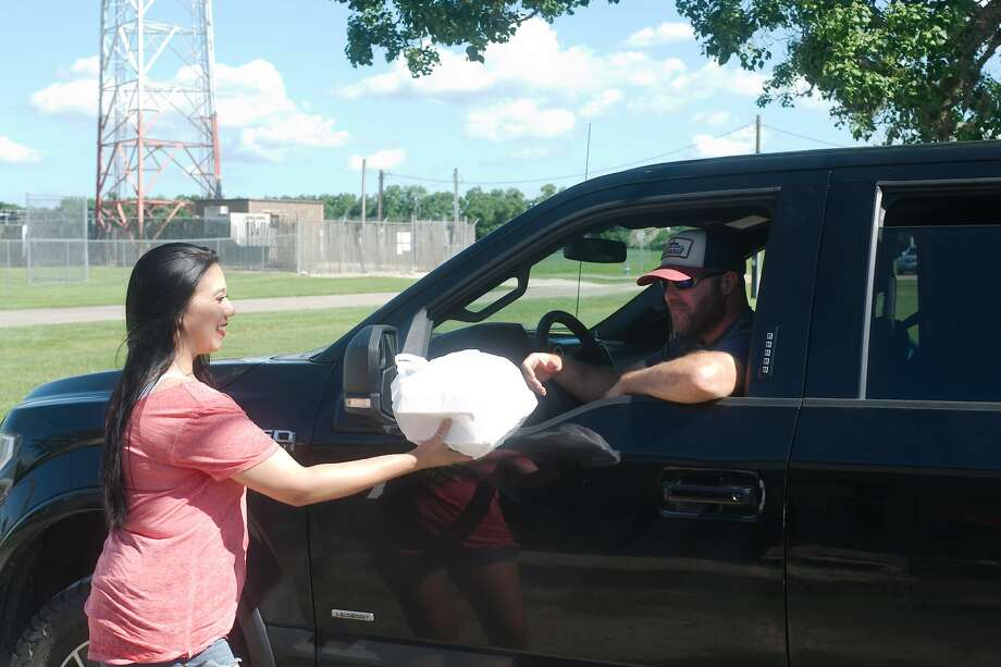 Misty Aldape delivers a fresh fried catfish dinner to Ben Baxley curbside at VFW Post 7109 in Pearland. Upon learning that the post was in danger of closing, residents contributed funds and have lined up each weekday to purchase food from the post's restaurant. Photo: Kirk Sides/Staff Photographer / ? 2020 Kirk Sides / Houston Chronicle