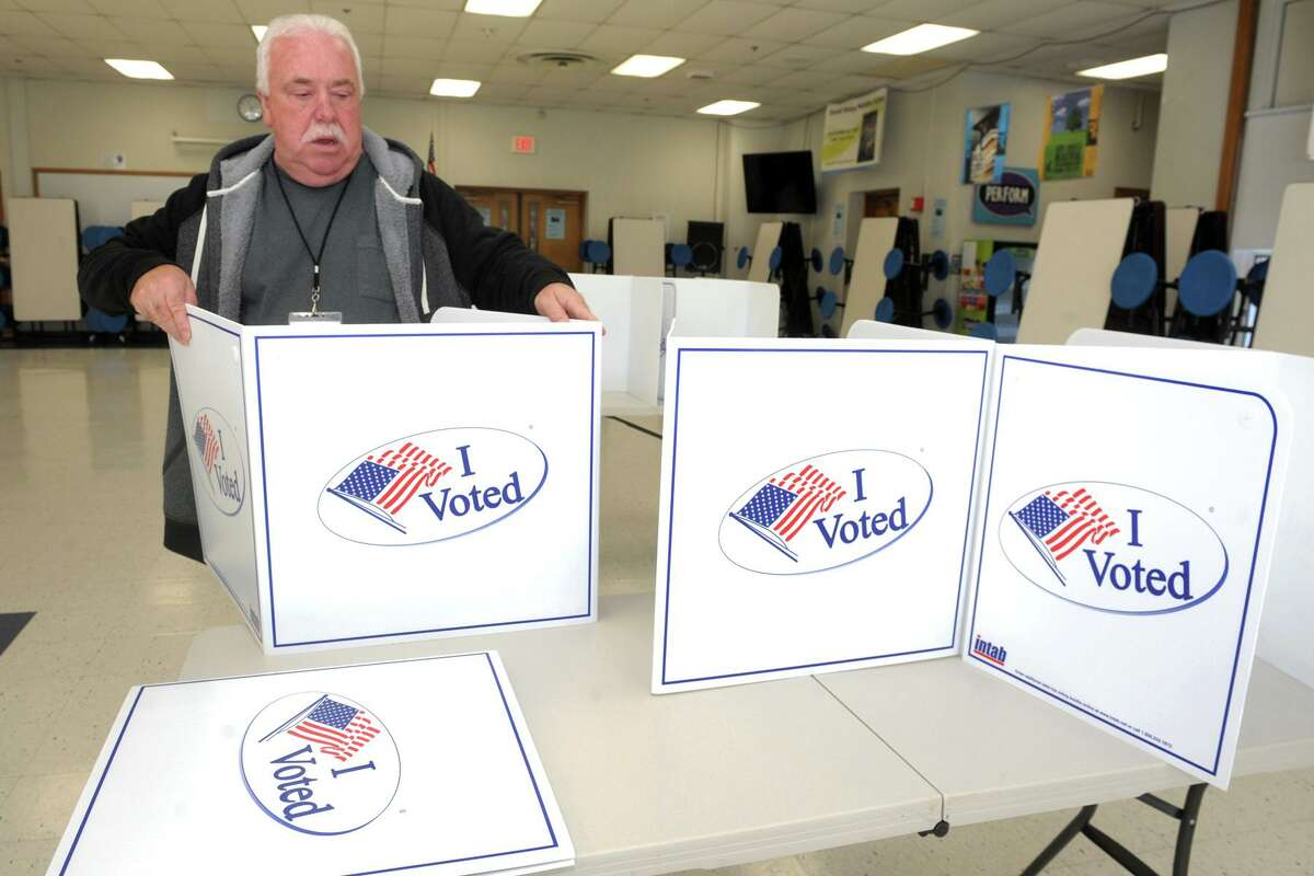 David Sigler assembles partitions while he and others prepare the cafeteria of Wooster Middle School for Election Day 2019 voting in Stratford.