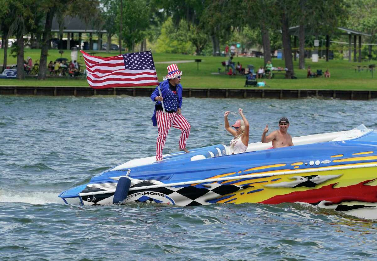 Chad Myers, left, dressed as Uncle Sam along with his wife, Holly Myers, and Ferrill Hill, right, participate in the Trump Boat Parade on Lake Conroe Saturday, June 6, 2020, in Conroe.