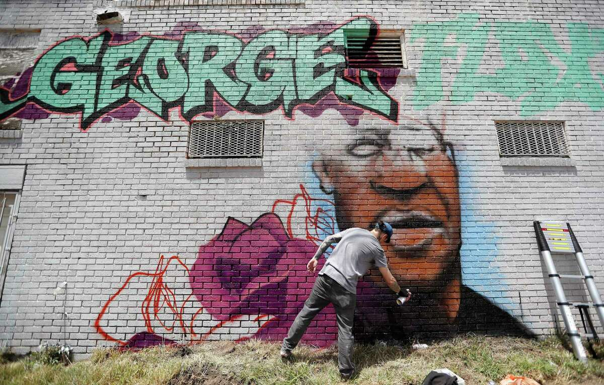 Artist Zack Murray works on a mural in memory of George Floyd at the corner of Elgin and Ennis, Saturday, June 6, 2020, in Houston. The project came about with Richard Johnson's non-profit Cinque Projects, with a paint donation from Home Depot, and permission from the building's owner. Cinque Projects works in the Third Ward neighborhood with entrepreneurs, specializing in space and art, and loaner lawnmower loaner programs.
