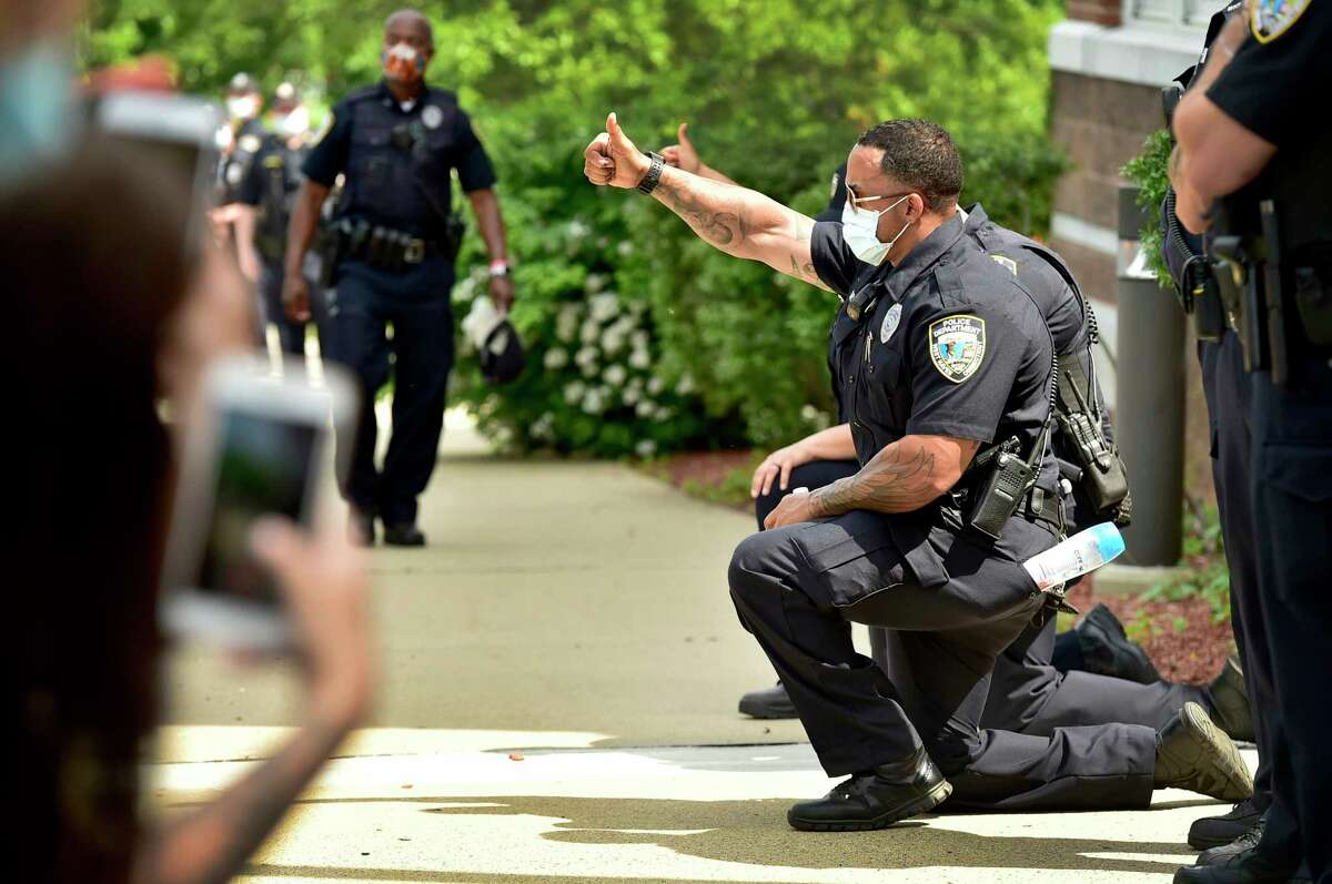 West Haven, Connecticut - Saturday, June 6, 2020: West Haven Police officers kneel in solidarity in front of approximately 675 demonstrators who rallied Saturday afternoon on the West Haven Green and then marched to the West Haven Police Department protesting police brutality including the death of Mubarak Soulemane of New Haven who was fatally shot by Connecticut StateTrooper Brian North just off Interstate 95's Exit 43 in West Haven on January 15, 2020. Soulemane allegedly had carjacked a driver in Norwalk following an alleged incident with a knife at a store there, then fled from police at high rates of speed along the highway.
