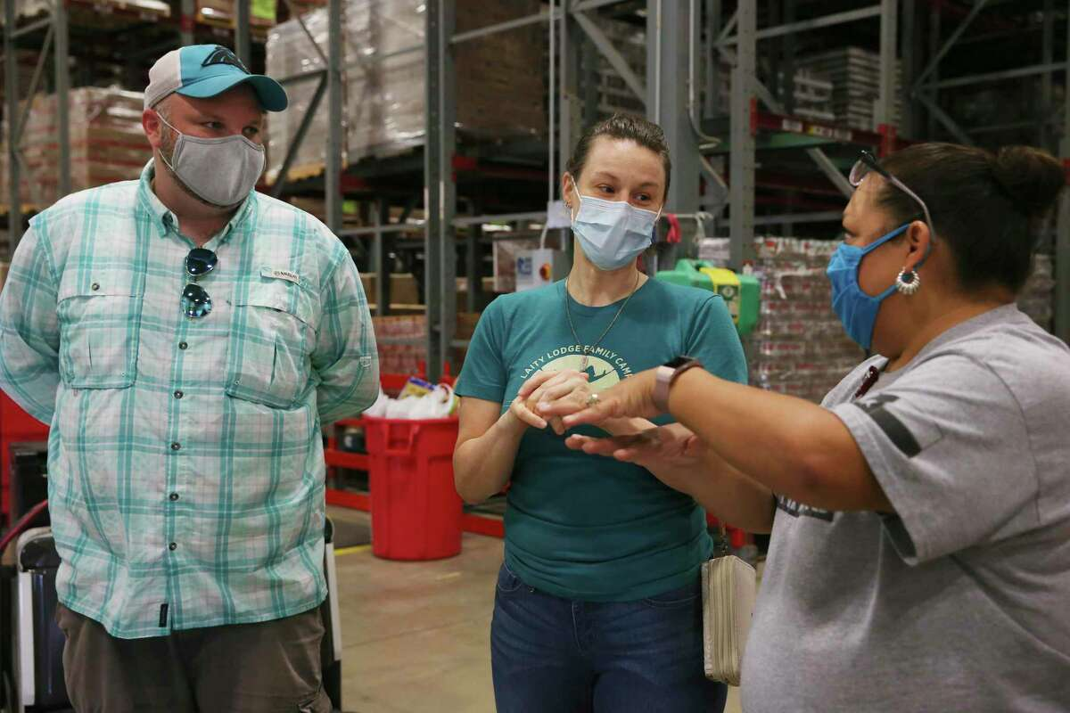 CRE8AD8 Dispatch Manager Lauren Lear, center, talks with Dayna Robokowski, the San Antonio Food Bank produce procurement manager, after delivering several pallets of produce boxes at the Food Bank on Friday, June 5, 2020.