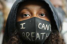 A girl wears a face mask during a Black Lives Matter rally in Parliament Square, in London, Saturday, June 6, 2020, as they protest against the killing of George Floyd by police officers in Minneapolis, USA. Floyd, a black man, died after he was restrained by Minneapolis police while in custody on May 25 in Minnesota. (AP Photo/Frank Augstein)