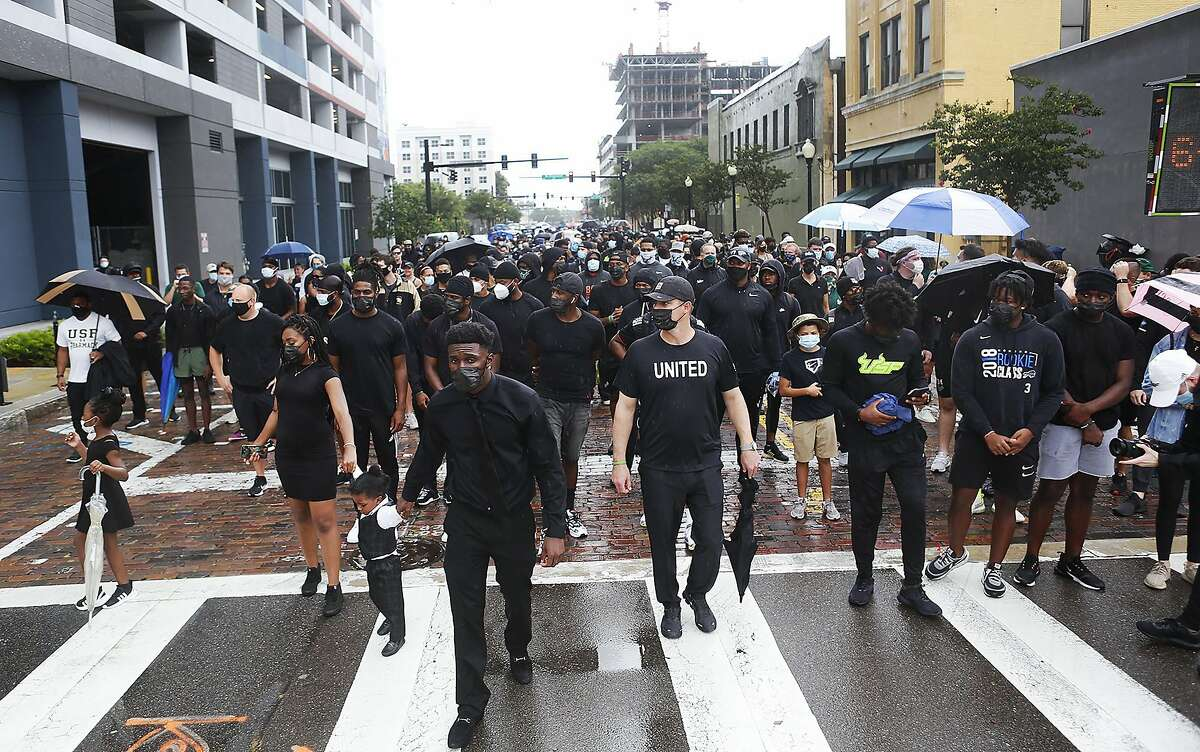 From left; Kiana Campbell, 24, walks with her daughter, Heaven Campbell, 6, and 2-year-old son King, along her partner KJ Sails, and USF football coach Jeff Scott during the unifying walk in memory of George Floyd and Martin Chambers, in Tampa, Florida, on Saturday, June 6, 2020. The death of George Floyd at the hands of police last month in Minneapolis has sparked nationwide protests for police reform. (Octavio Jones/Tampa Bay Times via AP)