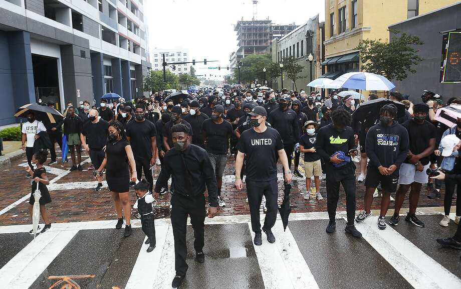 From left; Kiana Campbell, 24, walks with her daughter, Heaven Campbell, 6, and 2-year-old son King, along her partner KJ Sails, and USF football coach Jeff Scott during the unifying walk in memory of George Floyd and Martin Chambers, in Tampa, Florida, on Saturday, June 6, 2020. The death of George Floyd at the hands of police last month in Minneapolis has sparked nationwide protests for police reform. (Octavio Jones/Tampa Bay Times via AP) Photo: Octavio Jones, Associated Press