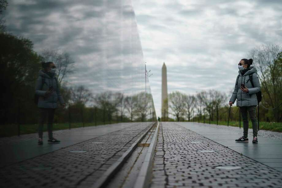 A woman visits an empty Vietnam Veterans Memorial in Washington, DC in April. Photo: Drew Angerer /Getty Images / 2020 Getty Images