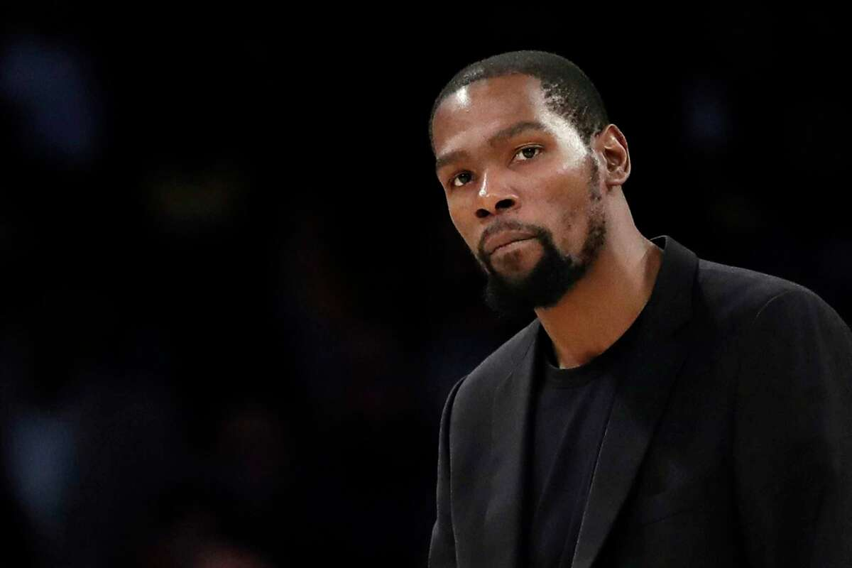 FILE- In this March 10, 2020, file photo, Brooklyn Nets' Kevin Durant watches during the second half of the team's NBA basketball game against the Los Angeles Lakers in Los Angeles. Durant is among the four Brooklyn Nets who have tested positive for the new coronavirus. A backlash roiled across social media Wednesday, March 18, as several celebrities and professional athletes revealed that they had been tested for the coronavirus, even when they didna€™t have a fever or other tell-tale symptoms. (AP Photo/Marcio Jose Sanchez, file)