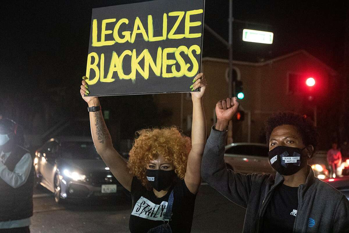 Protesters near the police station hold signs during a demonstration after Sean Monterrosa was shot and killed by a Vallejo police officer earlier in the week in Vallejo, Calif., Friday, June 5, 2020