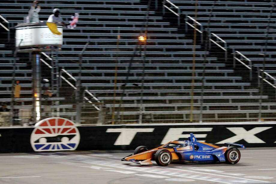 Scott Dixon earns the checkered flag as he crosses the finish line to win an IndyCar auto race at Texas Motor Speedway in Fort Worth, Texas, Saturday, June 6, 2020. (AP Photo/Tony Gutierrez) / Copyright 2020 The Associated Press. All rights reserved.
