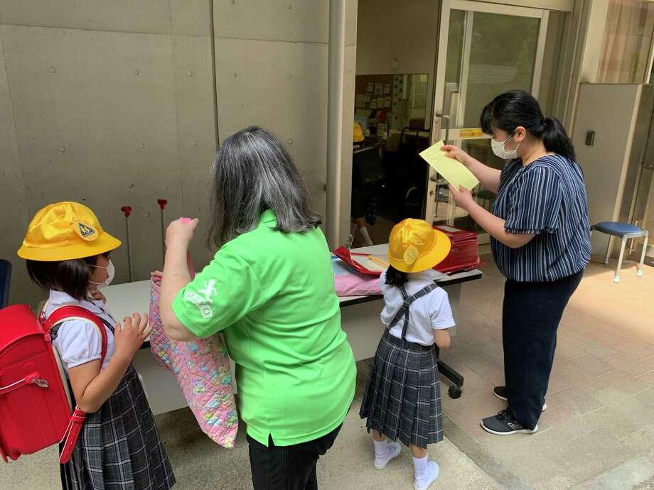 Children have their temperature charts checked as they arrive at Hoyonomori Gakuen, a school in Tokyo's Shinagawa ward, on June 3. Photo: Washington Post Photo By Simon Denyer / The Washington Post